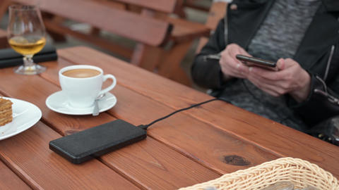 A woman connects her phone to a power bank for charging in a cafe Live Action