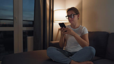 Woman with glasses sitting on the couch in a cozy room and using smartphone for Live Action