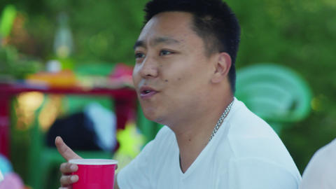 Close up of asian man singing with his friends. Group of friends sits on a Live Action