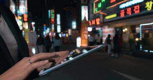 Woman browsing in web on pad in night Seoul, South Korea Footage