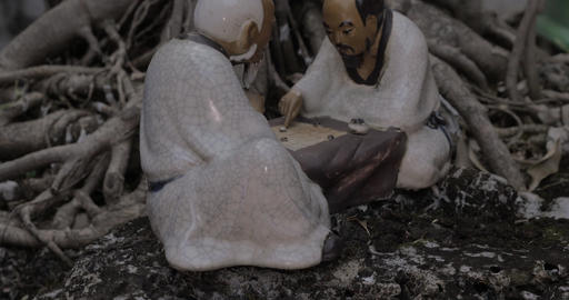 In roots of a tree in city of Hanoi, Vietnam stands a porcelain figurine Footage