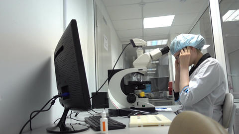 Young Researcher Using Microscope Footage