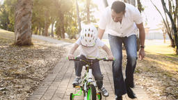 Tracking Shot of a Father Teaching His Son How to Ride a Bike Footage