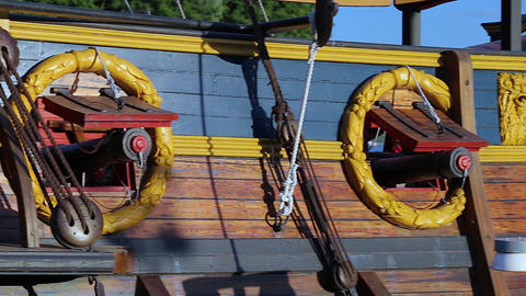 Vintage cannons stick out from the sides of an ancient ship. Panorama Live Action