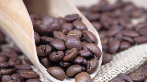 fresh coffee beans and spoon on wooden background Live Action