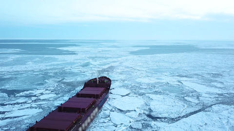 Aerial epic red ship in winter sails through frozen sea makes its way. Ice floe Live Action