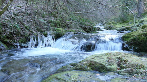 Icicles Hanging Over The Mountain Stream Flow Footage