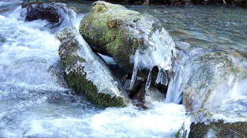 Ice over rock in cold mountain stream Footage