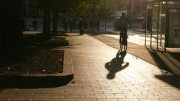 Bicyclist ride at empty sidewalk track, sunlit at early morning time Footage