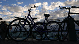 Citybikes attached to handrail, silhouetted view against cloudy evening sky Footage