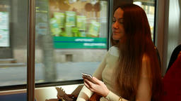 Woman sit in running tram, hold smartphone but look out… Stock Video Footage
