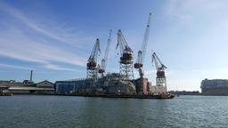 Dockyard establishing shot, large cranes around ship, seen across bay waters Footage