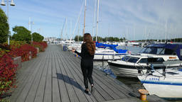 Slim woman come away along wooden pier, sunny day at yacht marina Live Action