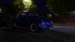 Old style Volkswagen Beetle parked on dark street, modern car drive by behind Footage