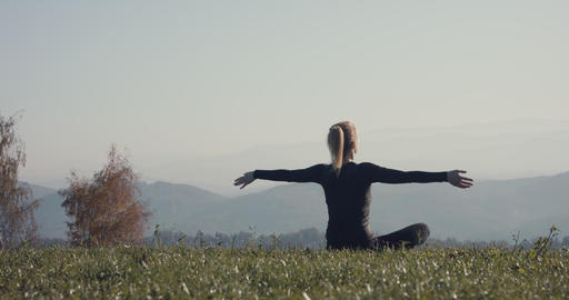 Young woman practice yoga meditation on a view after autumn hiking Live Action