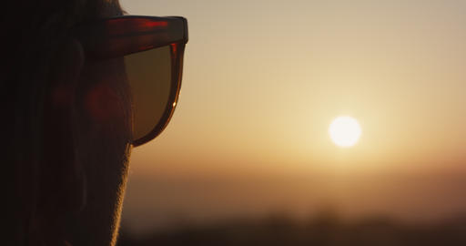 Woman with sunglasses blonde hair look at sunset silhouette close up Live Action