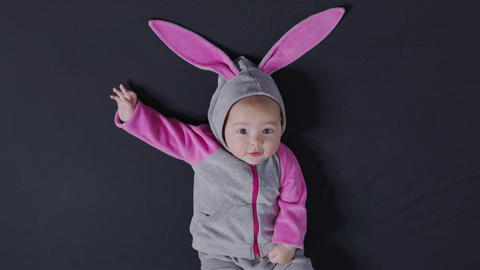 Cute baby smiling and looking in the camera close up. Little kid in Easter bunny Live Action
