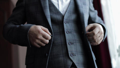 Buttoning jacket hands close up. Man in suit fastens buttons on his jacket Live Action