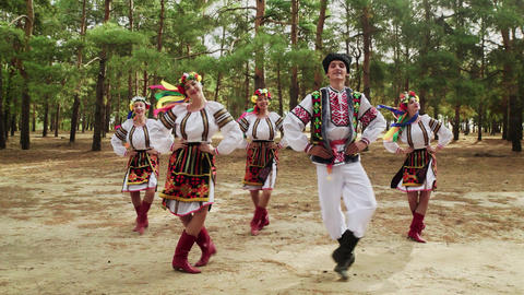 Four young women and one man in traditional costumes are dancing Ukrainian Live Action