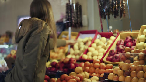 Back view of young woman chooses plums on store shelves at the market Live Action