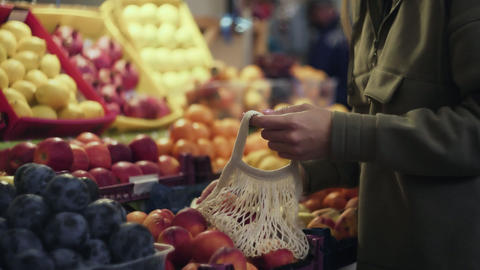 Young woman puts red fresh appless into string bag at market Live Action