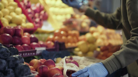 Young woman with blue gloves puts red fresh Garnets into string bag at market Live Action