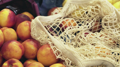 Top view of woman puts fresh peaches into string bag at market Live Action