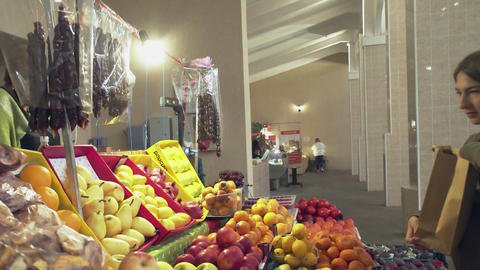 Young woman with a paper bag chooses fruits on store shelves at the market Live Action