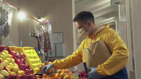 A man with protective mask and gloves chooses a fresh tangerines, puts them into Live Action