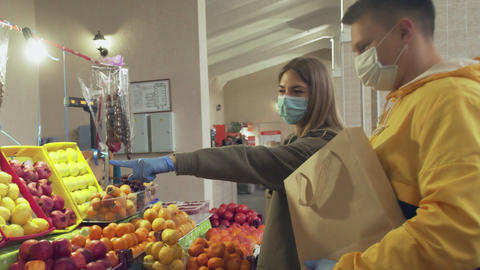 Young couple with protective mask and gloves chooses a fresh oranges, puts them Live Action