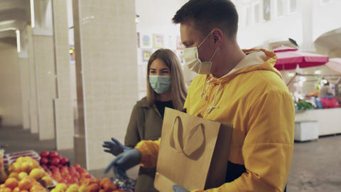 Young couple in protective mask and blue gloves quarreling at the market Live Action