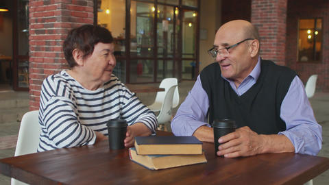 Elderly couple drinking tea or coffee in a street cafe Live Action