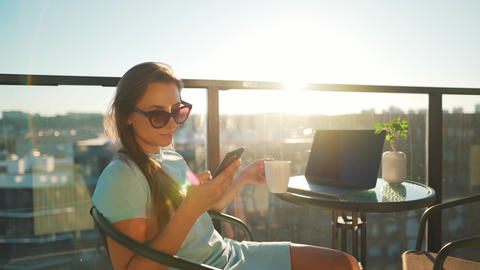 Woman using smartphone on the balcony against the backdrop of the sunset Live Action