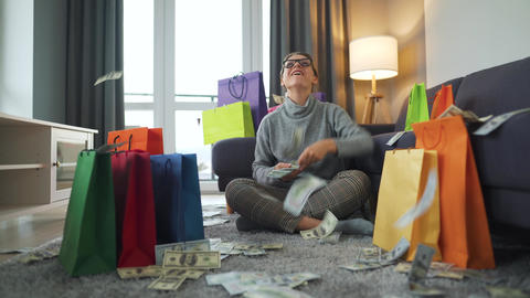 Happy woman is sitting on a carpet in a cozy room among shopping bags and making Live Action