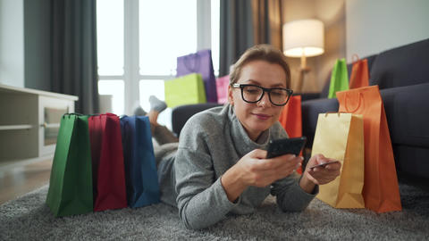 Happy woman with glasses is lying on the floor and makes an online purchase Live Action