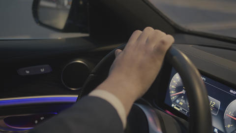 Closeup of male hands in costume on steering wheel car. Scene. Extreme close-up Live Action
