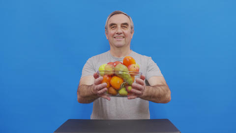 Portrait of Senior male Pensioner holding a variety of fruits. the concept of a Live Action
