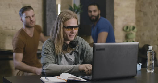 Excited Caucasian man in sunglasses surfing Internet on laptop and calling Live Action