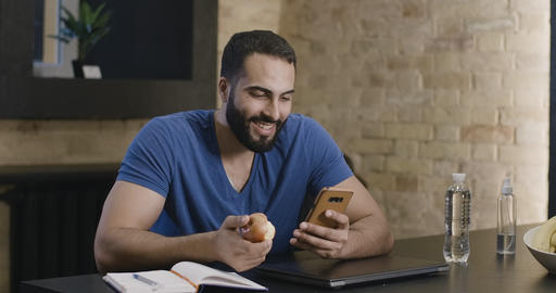 Handsome young Middle Eastern man surfing Internet on smartphone and eating Live Action
