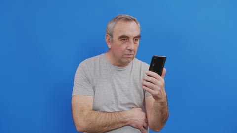Happy senior elderly man holding smart phone watching mobile video calling Live Action