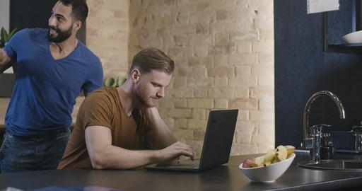 Absorbed young man surfing Internet on laptop as multiethnic friends coming and Live Action
