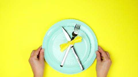 two female hands put metal knife and fork tied with yellow ribbon on empty plates Live Action