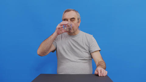Mature man taking pill drinking water having health problem. Pensive grandfather Live Action