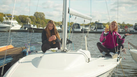 Young girls with smartphones sit on board an expensive sports yacht and take Live Action