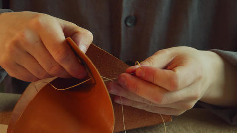 A professional tailor tanner sews an accessory attachment to a bag made of Live Action