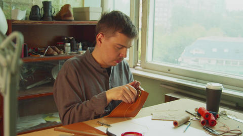 A young skilled tailor sews the element to a leather bag using a tailor's needle Live Action