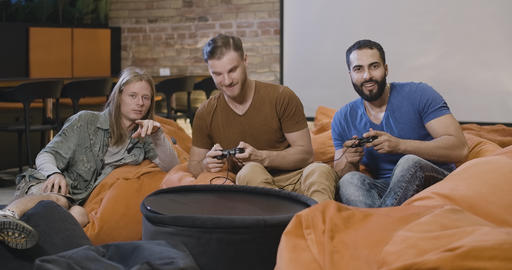 Cheerful multiethnic millennial colleagues playing with game consoles during Live Action