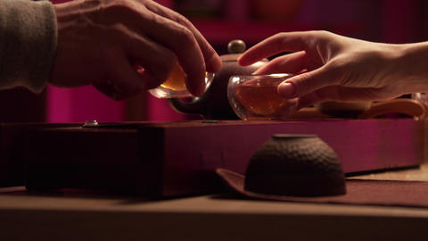 Hands of a man and a woman lift cups of natural aromatic amber tea from chaban Live Action
