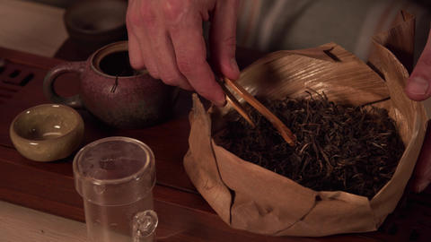 Close-up shot, a man puts dried tea leaves from a bag in a special ceramic Live Action
