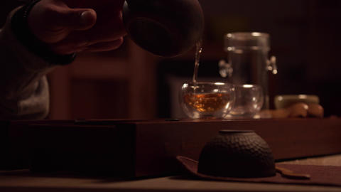 Close-up of the hand of an Asian master pouring tea into cups standing on the Live Action